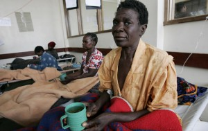 Cholera patients hold cups of sugar solution as they rest inside a ward Budiriro Polyclinic in Harare