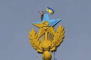 "A man takes a ""selfie"" as he stands with a Ukrainian flag on a Soviet-style star re-touched with blue paint so it resembles the yellow-and-blue national colours of Ukraine, atop the spire of a building in Moscow"