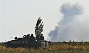 A Ukrainian army vehicle is seen against smoke from separatist artillery fire near Mariupol