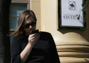 Woman passes by the headquarters of Sistema JSFC in Moscow