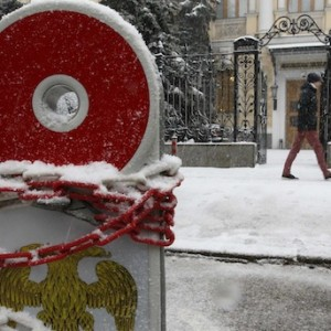 A chain is seen wrapped around a road sign for parking, with the coat of arms of the Central Bank seen on it, in Moscow