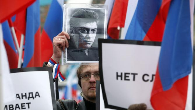 People hold placards to commemorate Kremlin critic Nemtsov in central Moscow