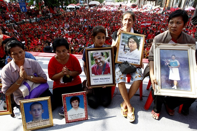 Relatives and representatives hold photos of those who died in 2010 government crackdown on red shirt protesters in Bangkok